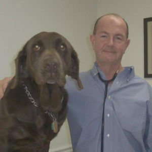 "Dr. McMahon and his 8 year-old Chocolate Labrador named ""Soy"""